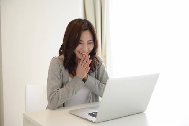 PCの前で喜ぶ女性